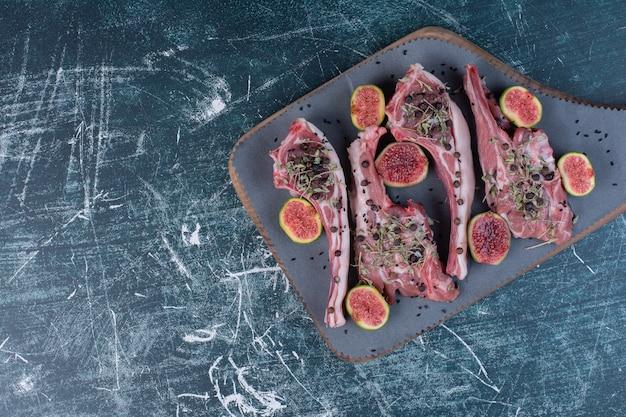 Rohe rippenkoteletts in holzbrett mit feigen und getrockneten kräutern.