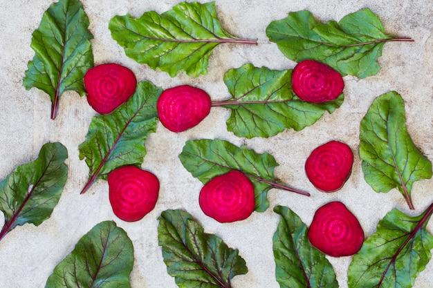 Rohe rote-bete-wurzeln geschnitten und mangold verlässt auf rustikalem brett