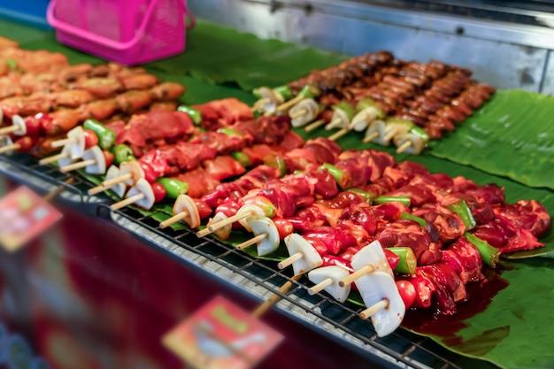 Rohe rote kebabs mit zwiebeln aus enten- und hühnerfleisch und schweinefleisch auf dem straßenmarkt von phuket. traditionelles thailändisches streetfood