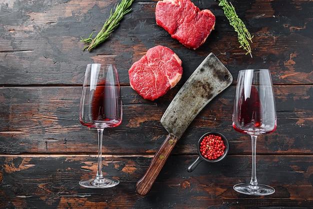 Rohe rumpsteaks mit metzgerbeil und zwei gläsern rotwein