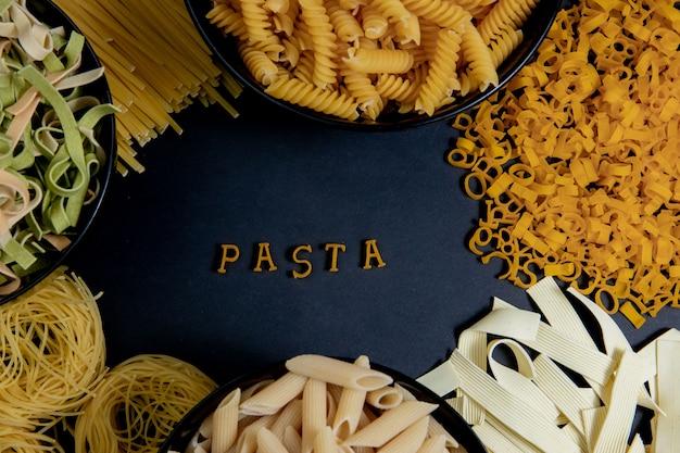 Rohe runde nudeln auf dunklem hintergrund. das wort pasta aus holzbuchstaben in der mitte. das konzept des leckeren essens. draufsicht, flache lage, kopierraum.