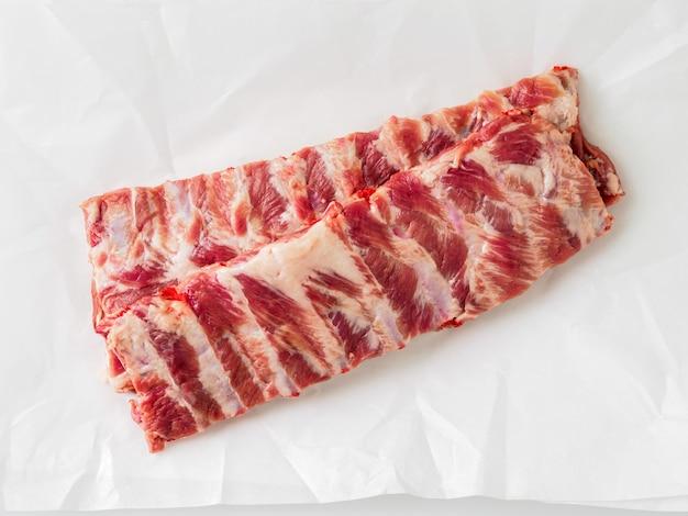 Rohe schweinefleischrippen auf weißem pergamentpapier, draufsicht