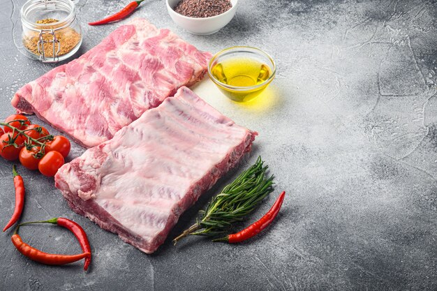 Rohe schweinefleischrippen mit zutaten für das kochset, auf grauem tisch