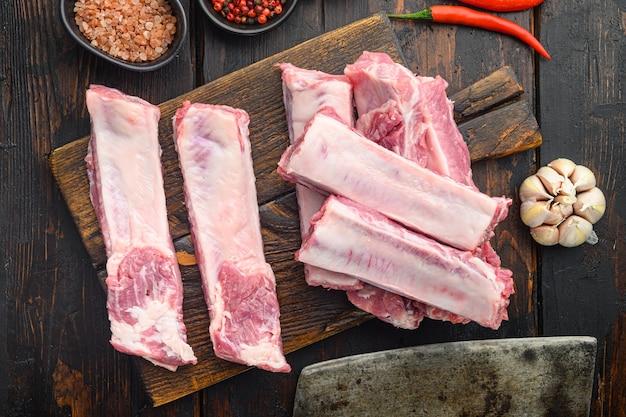Rohe schweinefleischrippen mit zutaten für das kochset, mit altem fleischbeilmesser, auf altem dunklem holztisch, draufsicht flach legen