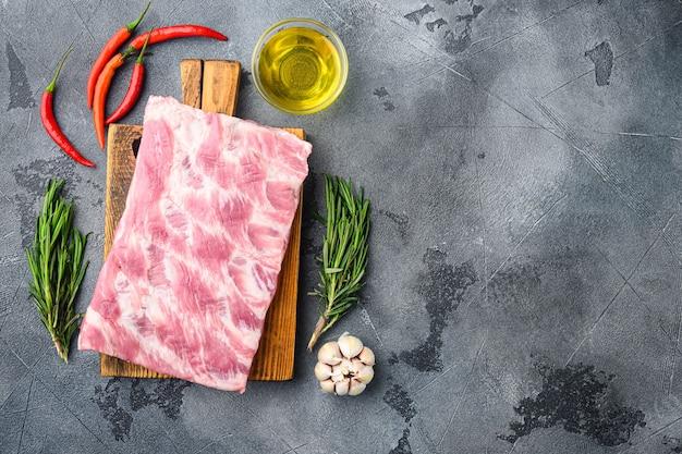 Rohe schweinefleischrippen mit zutaten für das kochset, mit honig, auf grauem tisch, draufsicht flach legen
