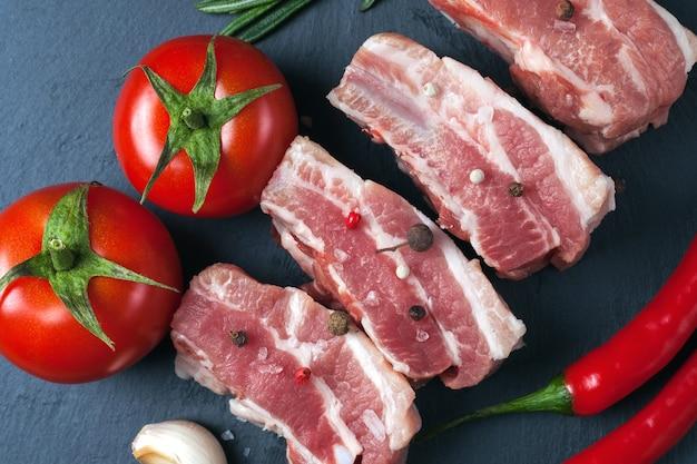 Rohe schweinefleischscheiben auf einem schwarzen schieferbrett, tomaten, rotem pfeffer und pulver. schweinebauch mit