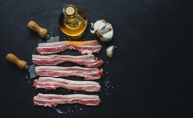 Rohe schweinefleischscheiben mit gewürzen im dunkeln. bereit zum kochen