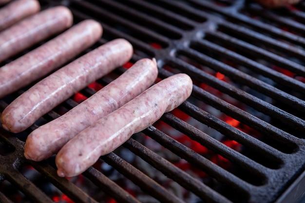 Rohe schweinefleischwürste, die auf grill auf einem sommerpicknick grillen