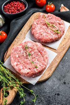 Rohe schweinekoteletts, hackfleischpastetchen auf einem schneidebrett. bio-hackfleisch. draufsicht