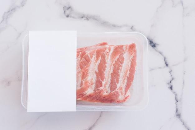 Rohe schweinerippchen in vakuumverpackung auf marmorhintergrund, logomodell für design.