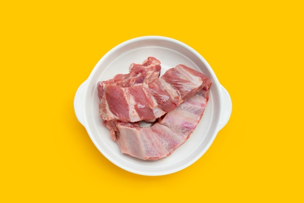 Rohe schweinerippchen in weißer platte auf gelbem hintergrund.