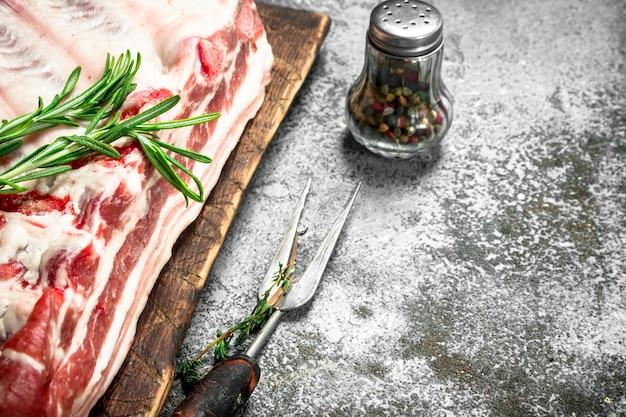 Rohe schweinerippchen mit kräutern und gewürzen. auf rustikalem hintergrund.