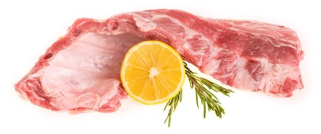 Rohe schweinerippchen mit rosmarin und zitrone auf einem weißen hintergrundisolat