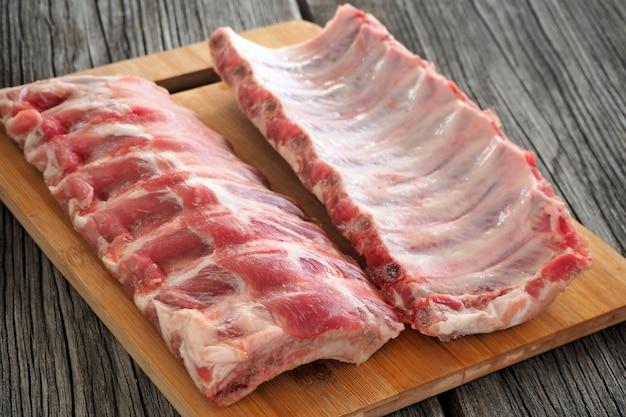 Rohe schweinerippchen zum grillen oder braten auf einem schneidebrett auf einem alten holztisch.