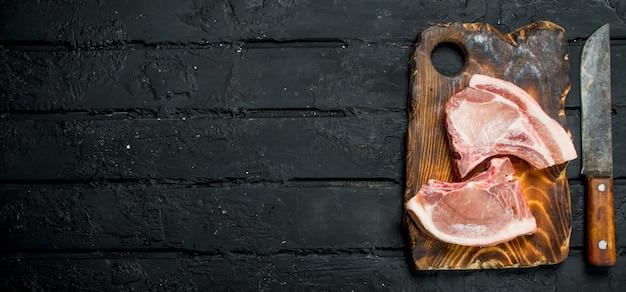 Rohe schweinesteaks auf dem knochen auf einem schwarzen rustikalen tisch.