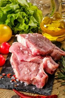 Rohe schweinesteaks auf steinbrett mit kräutern, tomaten und zitrone.