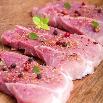 Rohe schweinesteaks mit gewürzen und kräutern bestreut. saftige rohe steaks für einen grill, abschluss oben.
