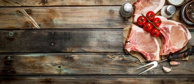 Rohe schweinesteaks mit tomaten und gewürzen. auf einem hölzernen hintergrund.