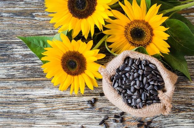 Rohe sonnenblumensamen im leinensack auf einem holztisch