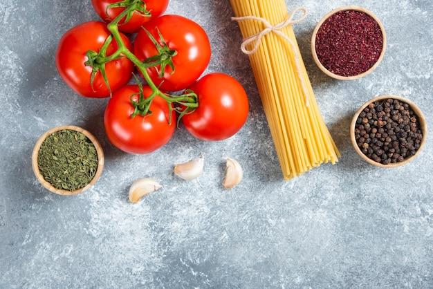 Rohe spaghetti, gewürze und tomaten auf marmorhintergrund.