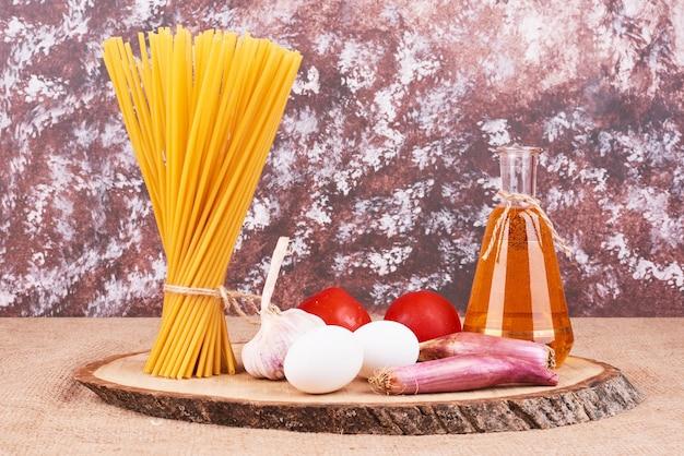 Rohe spaghetti mit zutaten auf einer holzplatte.