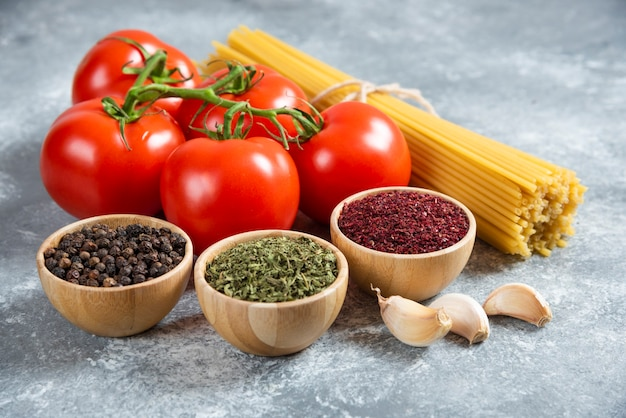 Rohe spaghetti-tomaten und gewürze auf marmoroberfläche