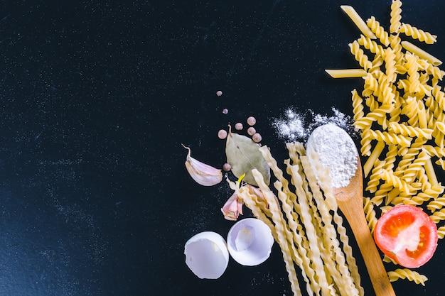Rohe spaghettis auf schwarzem hölzernem hintergrund, draufsicht