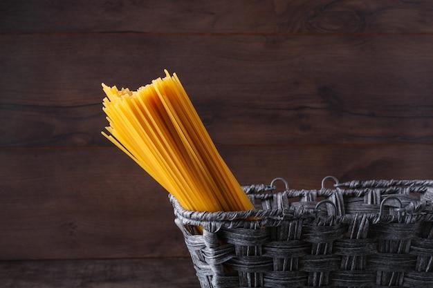 Rohe spaghettis im schwarzen korb auf holzoberfläche