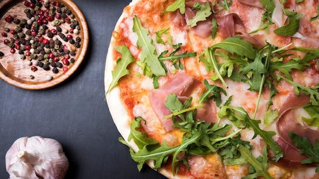 Rohe speckpizza mit schwarzem pfeffer und knoblauchknolle über schwarzer oberfläche
