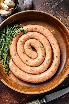 Rohe spiralförmige grillhähnchenfleischwurst. dunkler hintergrund.