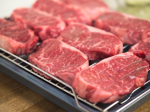 Rohe steaks auf einem rost zum braten vorbereitet.