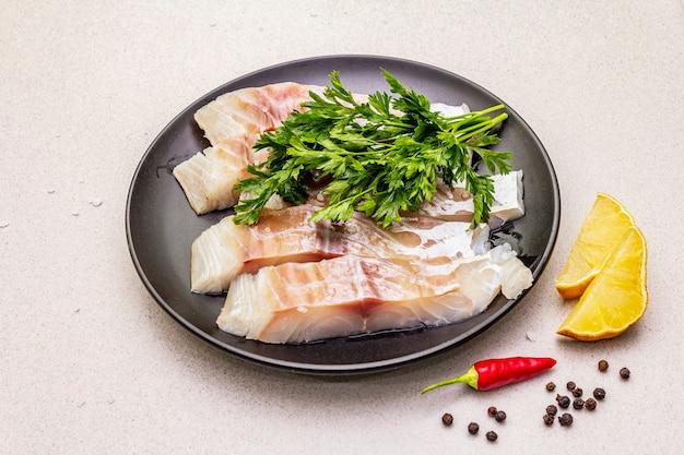 Rohe stücke des pollocks (pollachius virens). frischer fisch für einen gesunden lebensstil. zitrone, petersilie, meersalz, chili, schwarzes pfefferkorn