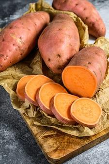Rohe süßkartoffeln auf einem hackenden brett, organische jamswurzel.