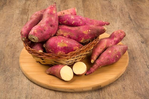 Rohe süßkartoffeln auf hölzerner raumnahaufnahme. frisches gemüse.