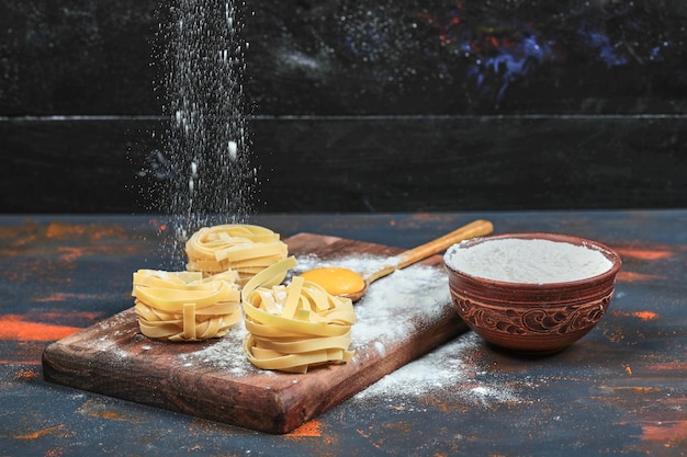 Rohe tagliatelle-nudeln auf holzbrett mit schüssel pulver.
