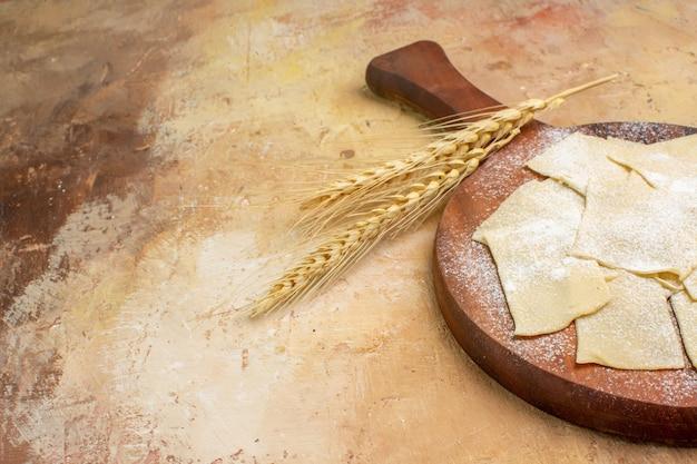 Rohe teigscheiben der vorderansicht mit mehl auf einem hölzernen schreibtisch