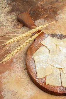 Rohe teigscheiben der vorderansicht mit mehl auf einer sahne-schreibtischnudelgerichtküche
