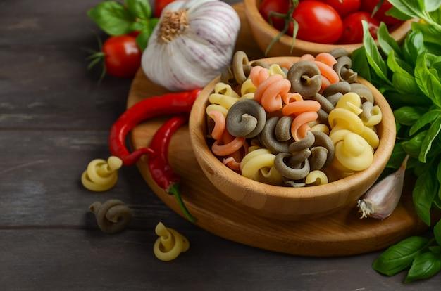 Rohe teigwaren mit frischen kirschtomaten, basilikum, paprikapfeffer und knoblauch für italienisches essen.