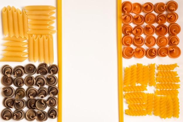 Rohe teigwaren unterschiedlicher art, form und farbe werden durch rohe teigwaren in quadrate unterteilt. in der mitte ist platz für eine inschrift