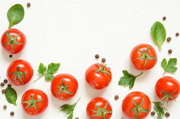 Rohe tomaten, kräuter und schwarzer pfeffer auf einem hellbetonierten hintergrund
