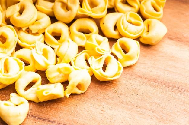 Rohe tortellini auf dem holzbrett, zum kochen vorbereitet