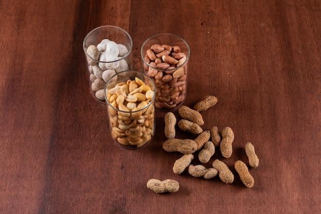 Rohe und gebratene erdnüsse in gläsern auf horizontalem