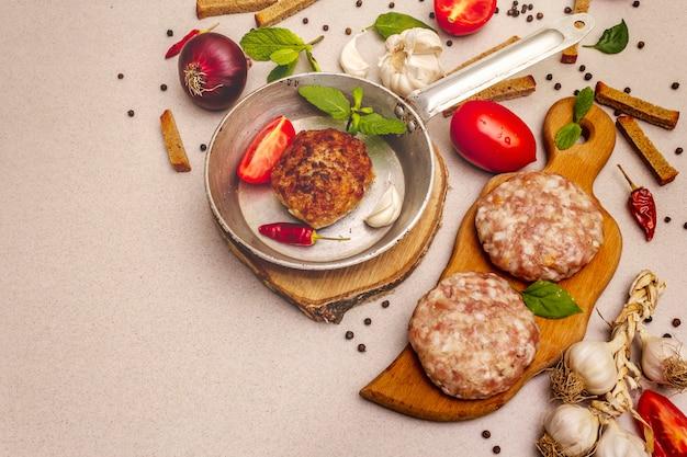 Rohe und gebratene schnitzel, frisches gemüse, gewürze, olivenöl. weinlesepfannen-, picknick- oder grillkochkonzept