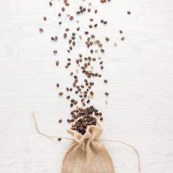 Rohe und geröstete kaffeebohnen, die vom kleinen sack auf schreibtisch fallen