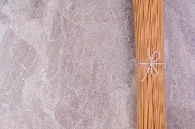 Rohe und ungekochte nudeln isoliert auf der marmoroberfläche