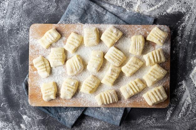 Rohe ungekochte hausgemachte kartoffelgnocchi mit mehl auf schneidebrett.