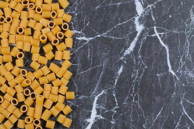Rohe ungekochte pasta penne auf steinschwarz.