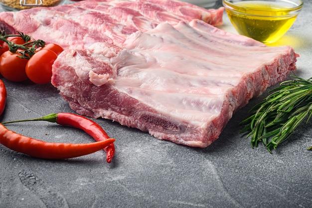 Rohe ungekochte schweinerippchen, frisches fleisch mit zutaten, auf grauem tisch