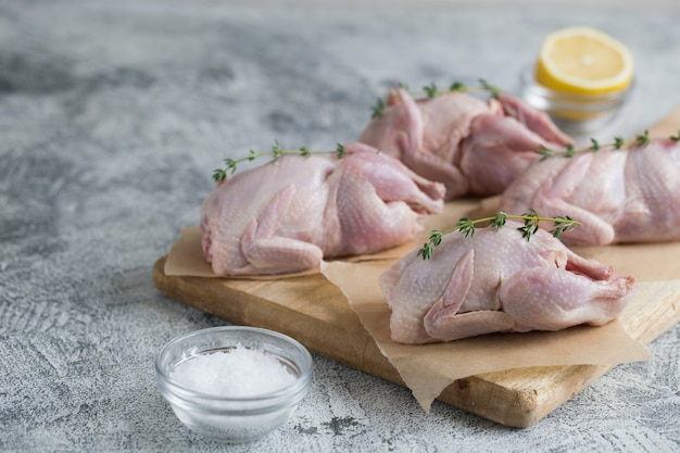 Rohe ungekochte wachtel. wachteln des rohen fleisches bereit zum kochen auf einem schneidebrett mit kopienraum