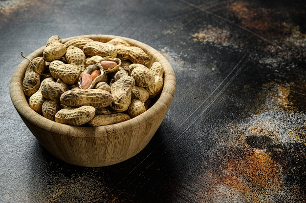 Rohe ungeschälte erdnüsse in der schale. bio-erdnuss. schwarzer hintergrund. der blick von oben. platz für text